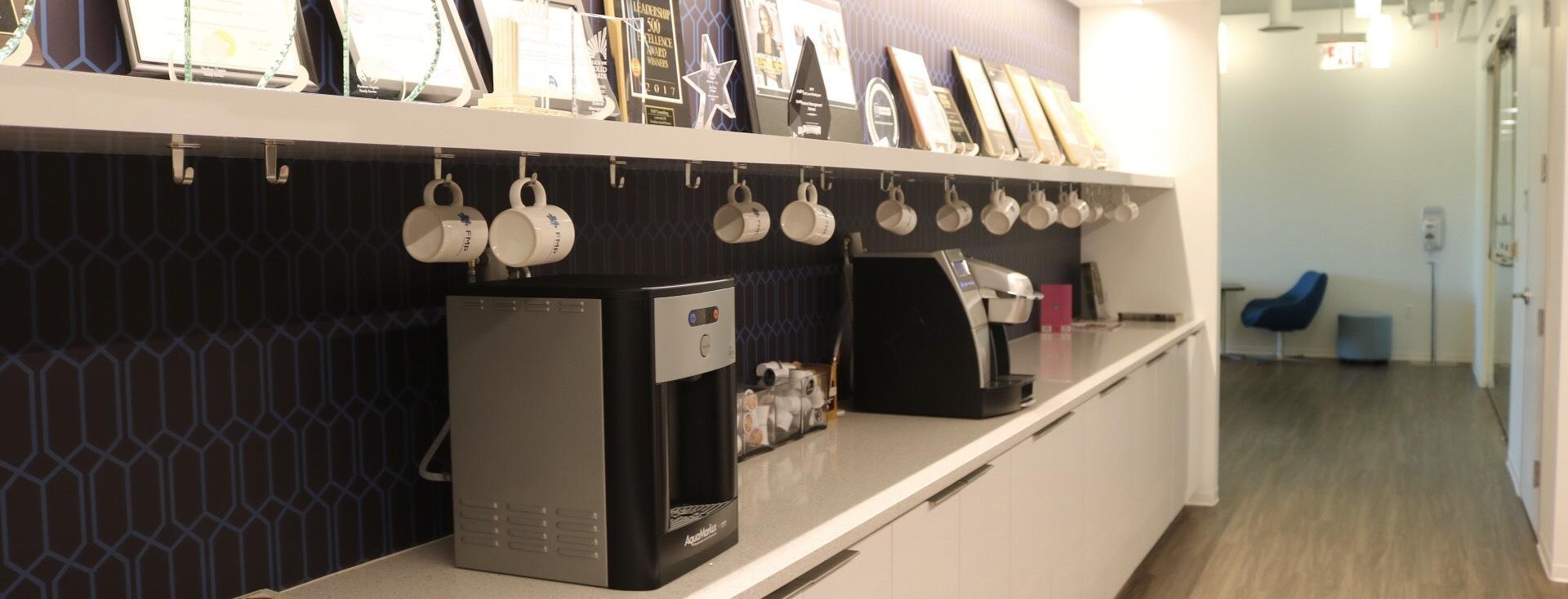 Photo of FMP office space, focusing on keurigs and coffee mugs