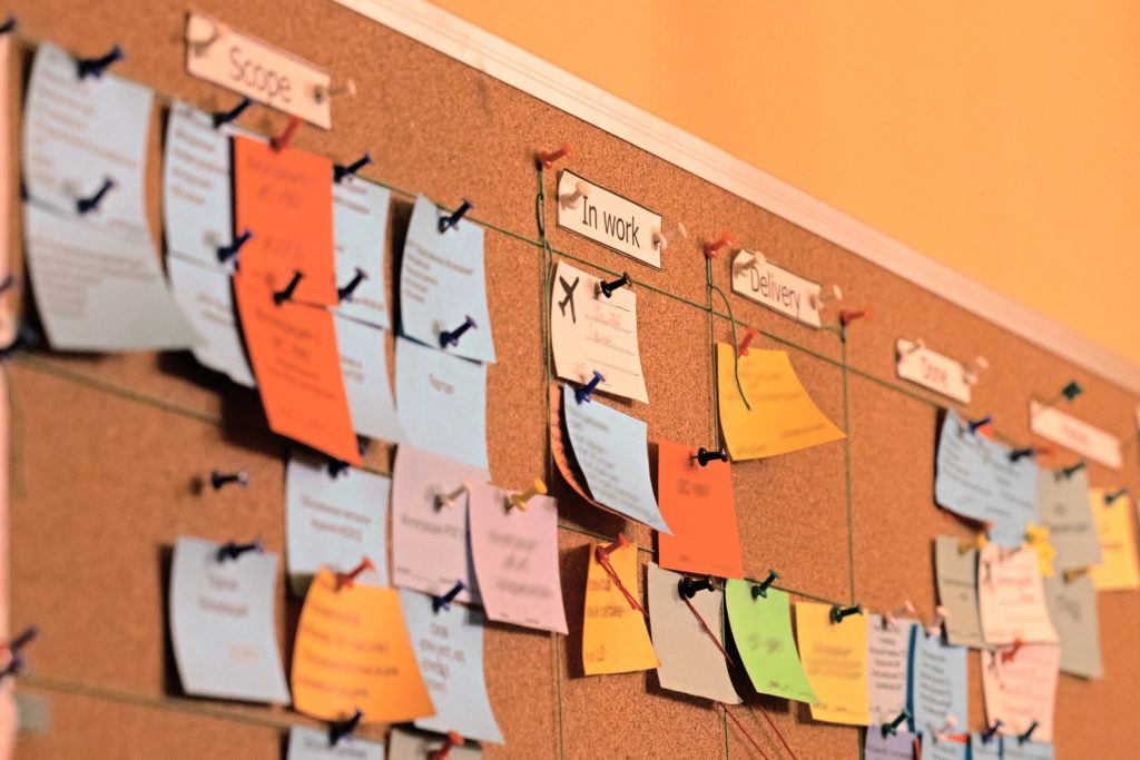 """Close up of a Kanban board with sticky notes on it representing the scrum agile agile development methodology. There are columns labeled """"Scope,"""" """"In work, and """"Delivery"""""""